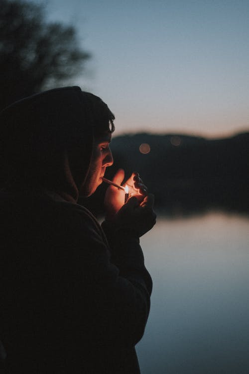 Man in Black Hoodie Smoking Cigarette on Front of Lake