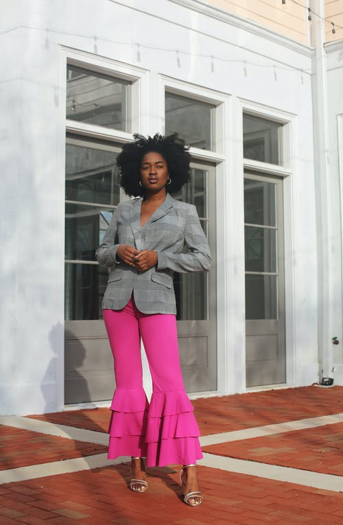 Woman in Gray Button Up Shirt and Pink Pants Standing Beside White Wall