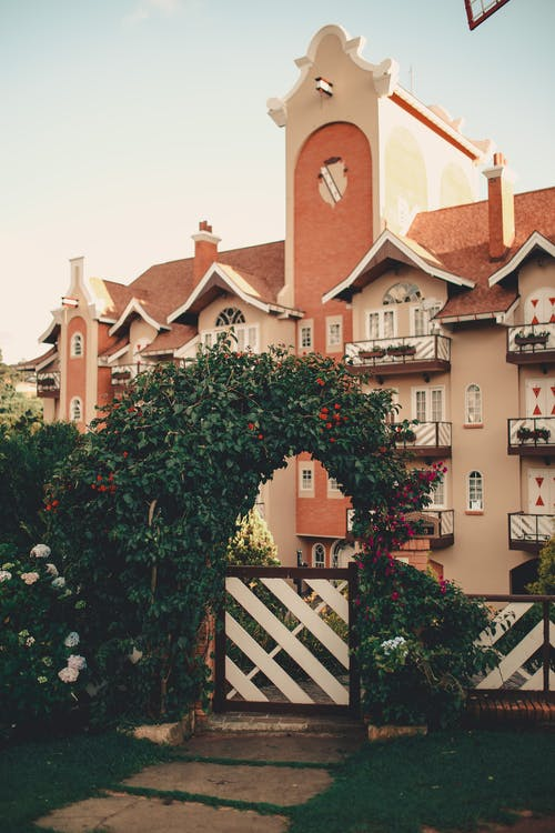 Facade of modern residential house with balconies and tower on middle built in old style located in yard behind fence decorated with green plants