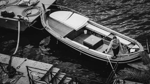Grayscale Photo of Man in a Boat on a River