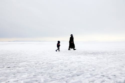 Two People Walking on Snow Covered Ground