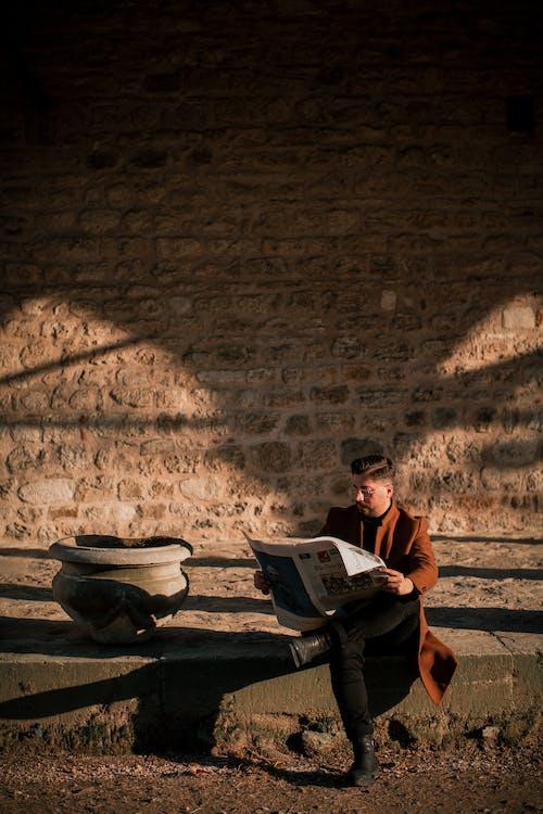 Man Sitting On Sidewalk While Reading A Newspaper