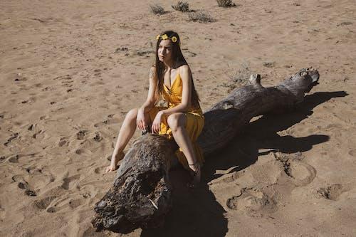 Woman in Yellow Dress Sitting on Trunk