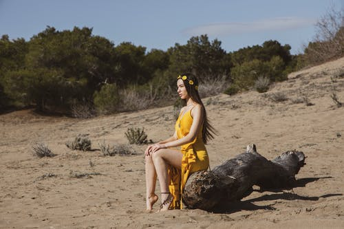 Woman in Yellow Dress Sitting on Wood