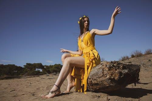Woman in Yellow Sleeveless Dress Sitting on Wood
