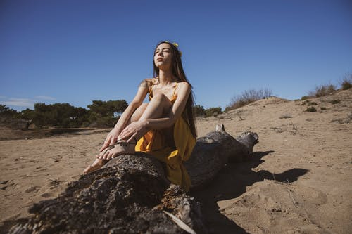 Woman in Yellow Dress Sitting on A Driftwood