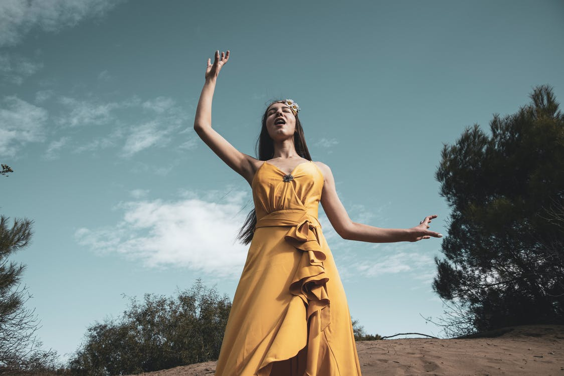 Woman in Yellow Sleeveless Dress Standing on Brown Sand
