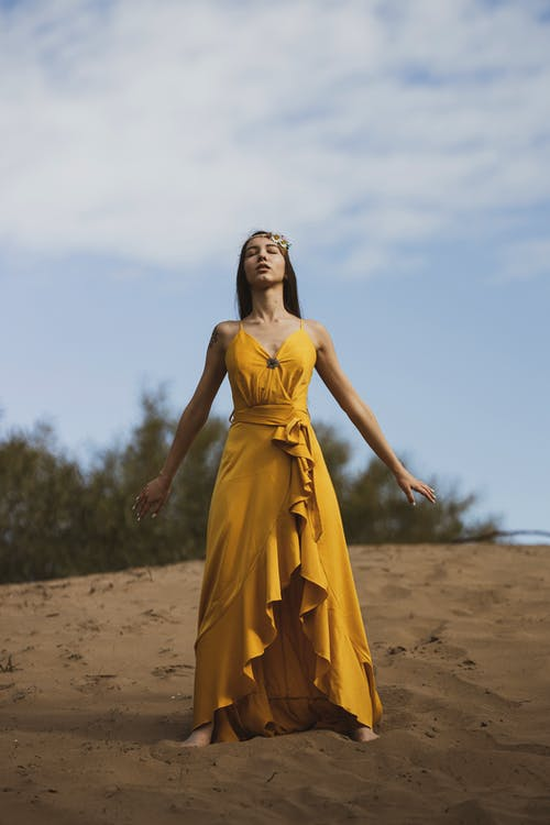 Woman in Yellow Dress Standing on Brown Sand