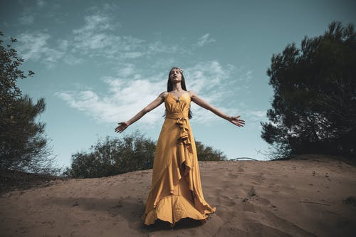 Photo of Woman in Yellow Dress Standing on Brown Sand Under Blue Sky with her Eyes Closed and Her Arms Spread