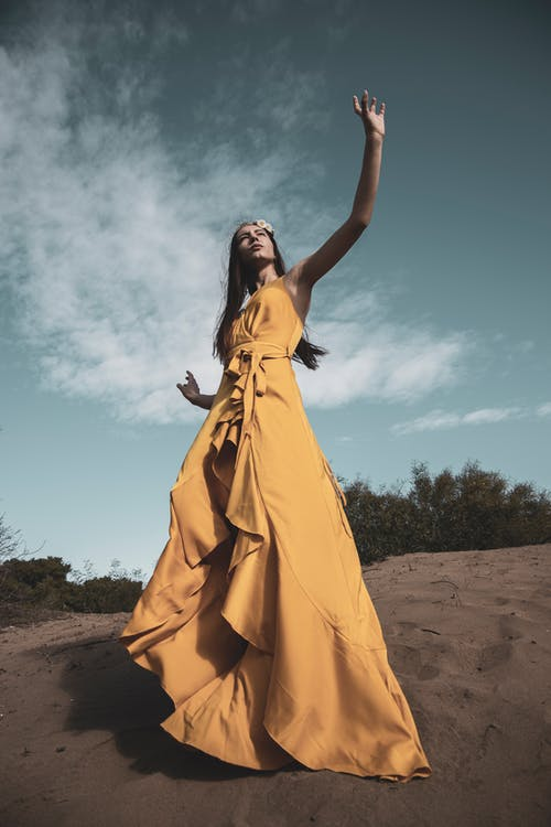Woman in Yellow Dress Standing on Brown Sand Under Blue Sky