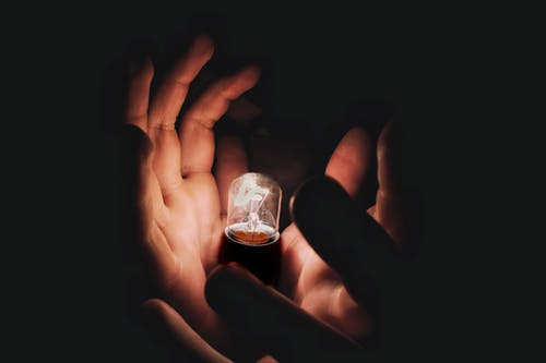 Crop person holding burning lightbulb in darkness