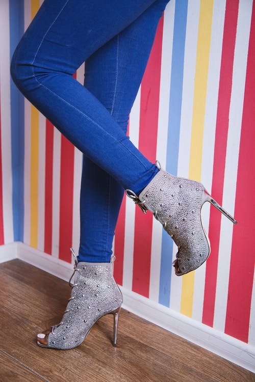 Woman in Blue Denim Jeans and Gray Heeled Shoes