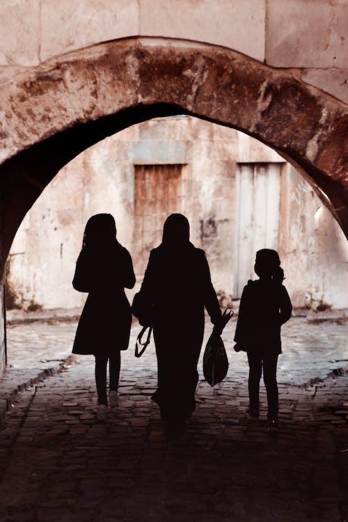 Silhouette of 3 Women Walking on Tunnel