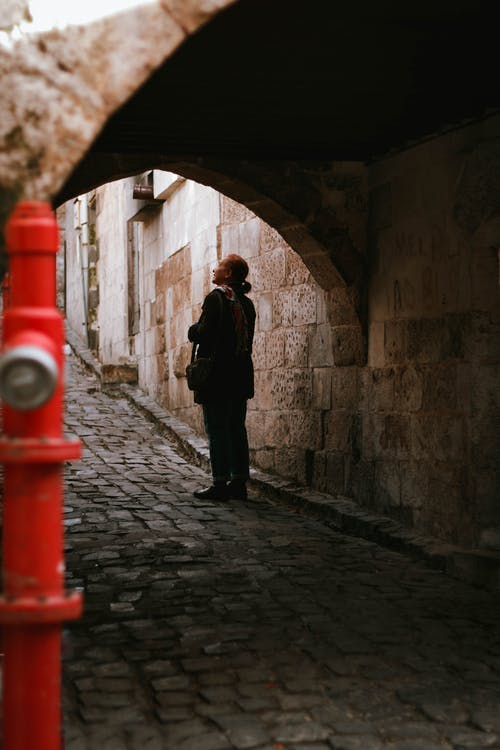 Woman Standing on  Arched Pathway