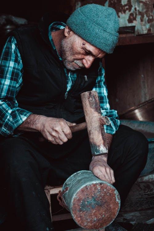 Ein älterer Mann, Der Eine Dose Mit Einem Hammer Repariert