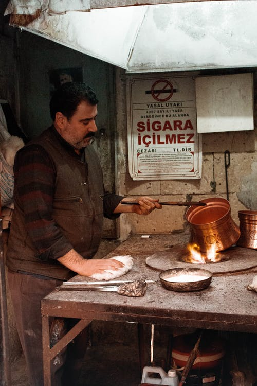Side view concentrated ethnic craftsman in dirty casual wear burning copper ware in fire in messy workshop