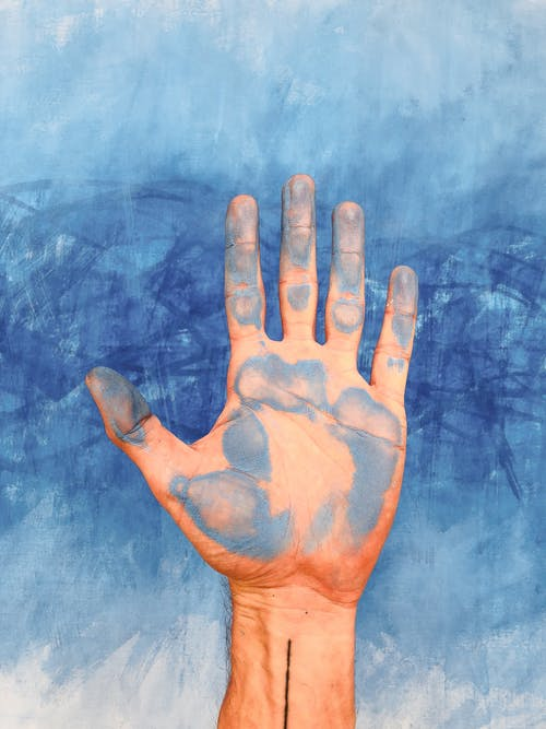 Persons Left Hand on Blue Textile