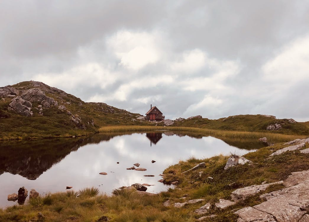 Cabin on Green Grass Field Near Lake Under White Clouds