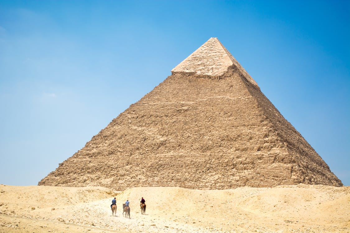 People Riding A Camel Near Pyramid of Giza Under Blue Sky