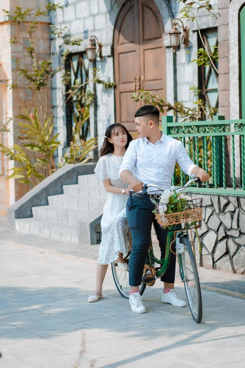 Man and Woman Riding Green Bicycle