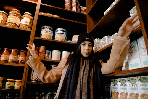 Woman in Black Knit Cap Behind Wood Shelves
