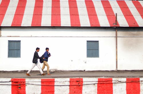 Side view of young Asian guys walking on platform painted with white and red stripes along shabby stone building with striped white and red roof on daytime