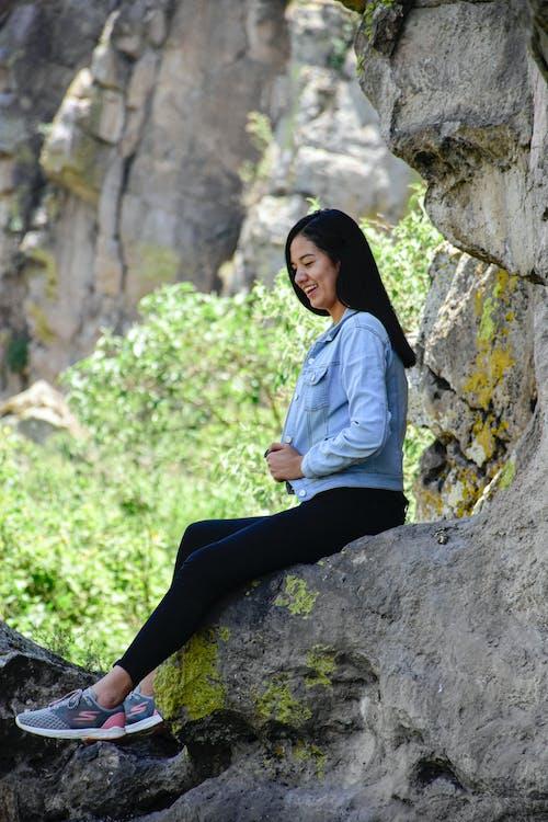 Woman in Blue Denim Long Sleeve Sitting on Rock
