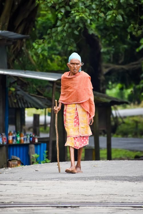 Photo Of An Old Woman Walking Barefoot