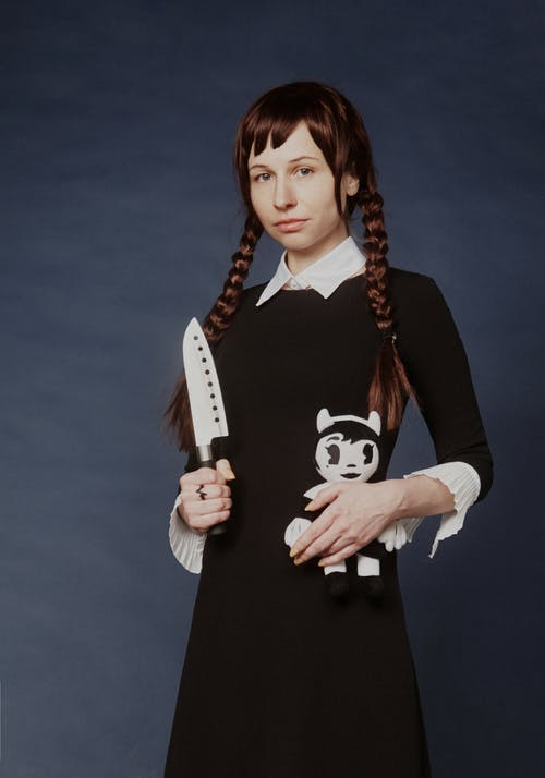 Woman Wearing Black Dress While Holding a Knife and Doll