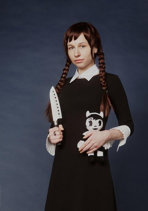 Mujer Vestida De Negro Mientras Sostiene Un Cuchillo Y Una Muñeca