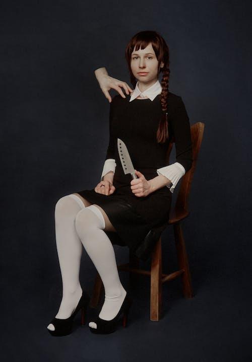 Woman in Black Long Sleeve Dress Holding A Metal Knife
