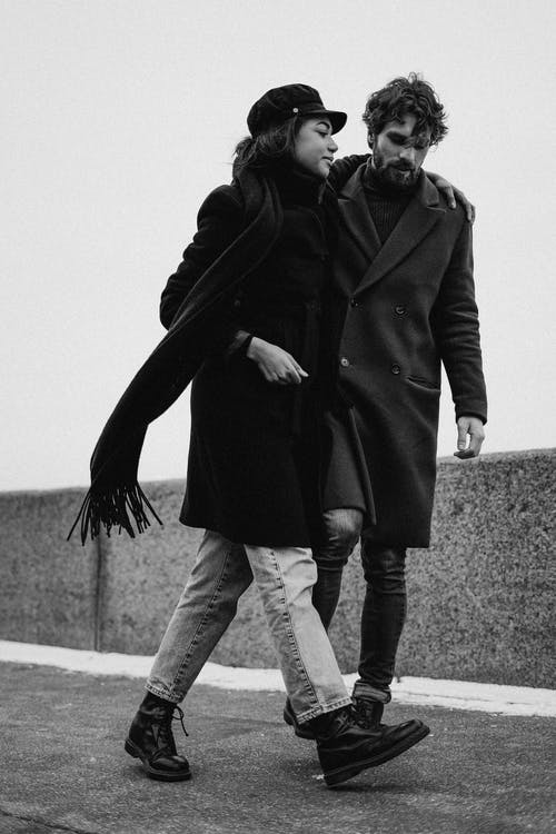 Man and Woman in Black Coat Walking on Gray Concrete Pavement