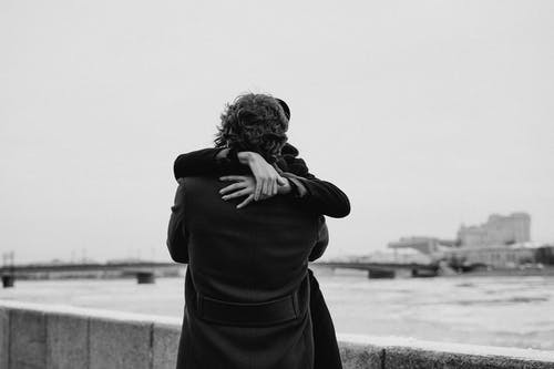 Grayscale Photo of Man Wearing Black Coat Hugging His Woman