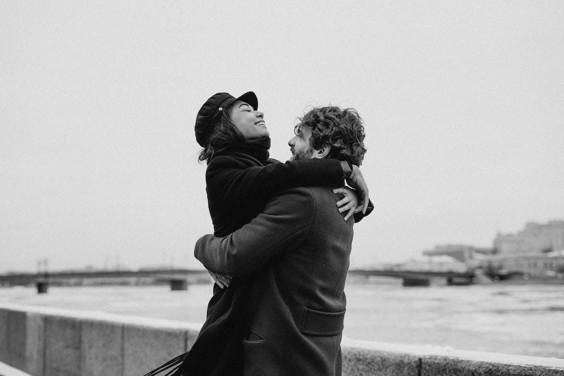 Monochrome Photo of Man Hugging His Woman