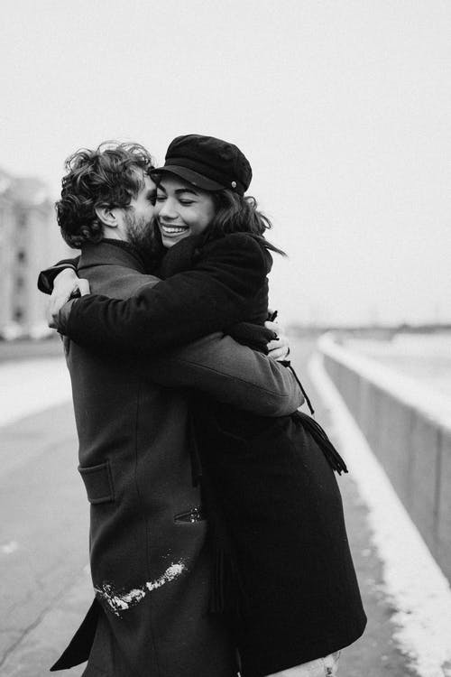 Man in Black Jacket Kissing Woman in Black Coat