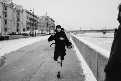 Laufende Frau Auf Dem Bürgersteig, Die Schwarzen Mantel Trägt