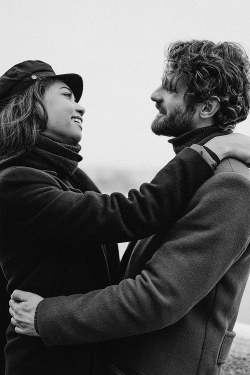 Monochrome Photo of Man and Woman Hugging While Looking to Each Other