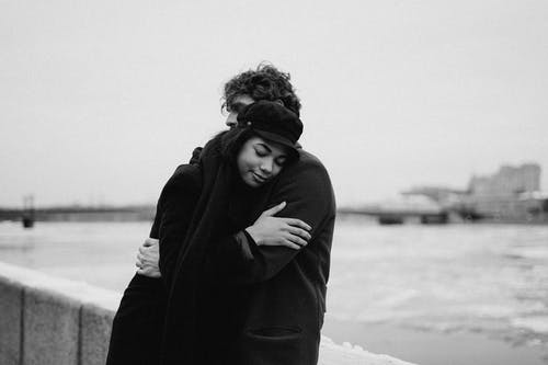 Grayscale Photo of Couple Hugging Each Other