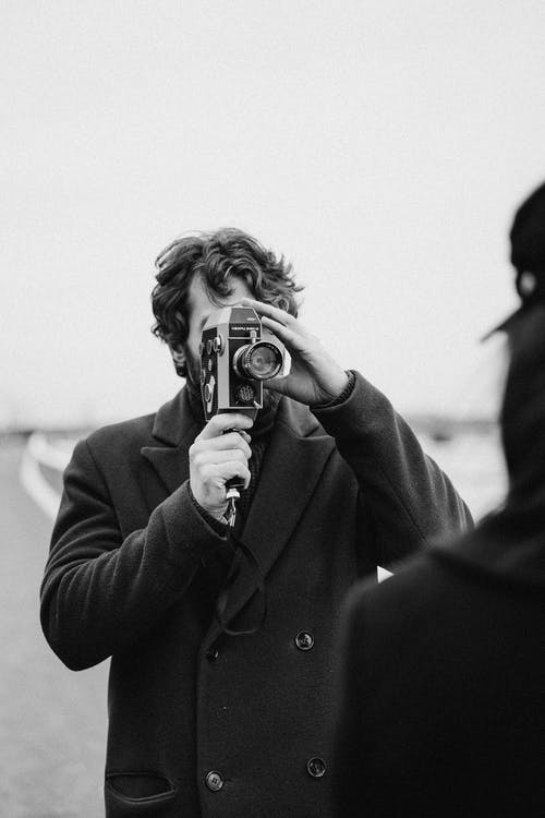 Gray Scale Photo of Man Holding Analog Camera