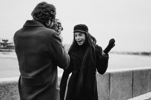 Grayscale Photo of Man and Woman in Black Coat