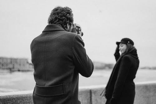 Man in Black Coat Taking Photo