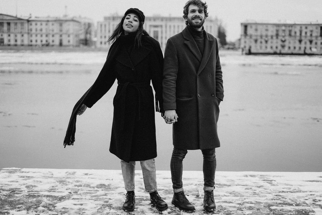 Man and Woman Holding Hands on Black and White Photography