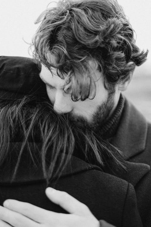 Grayscale Photo of Man Hugging Person