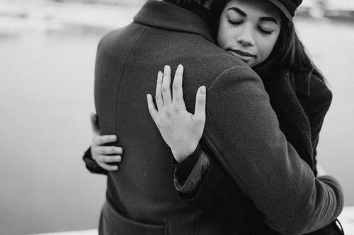 Monochrome Photo of Woman Hugging Her Man