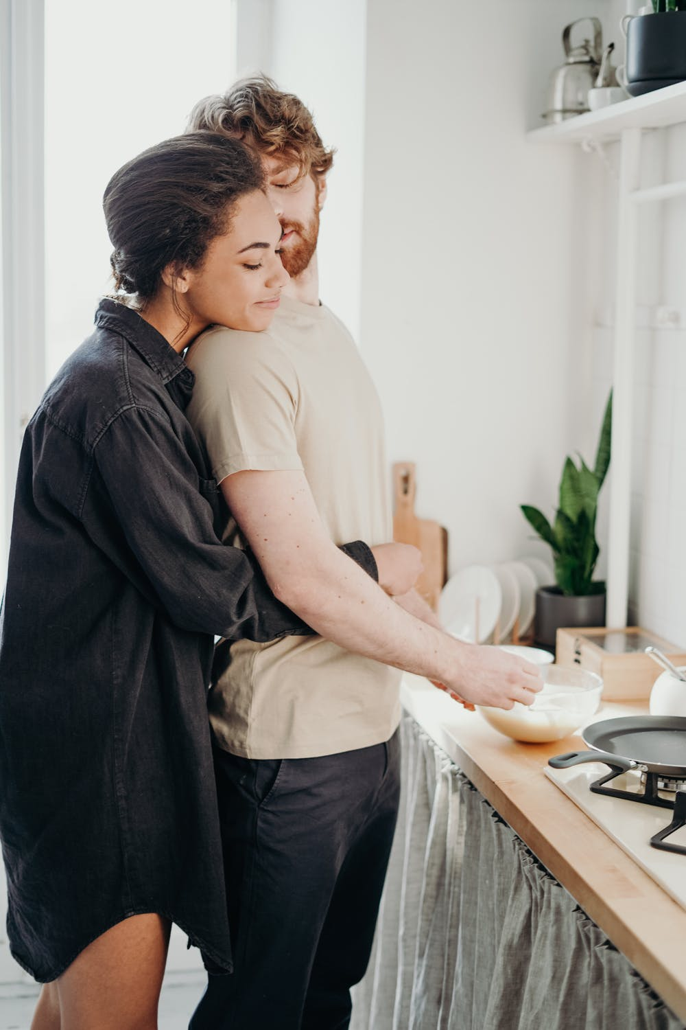 Woman hugging her man in the kitchen.   Photo: Pexels