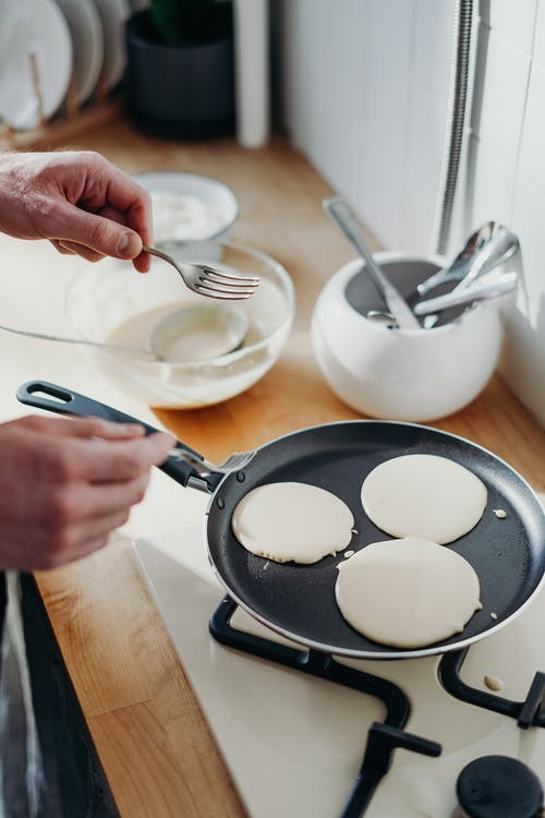 Person Cooking Pancake on Black Frying Pan