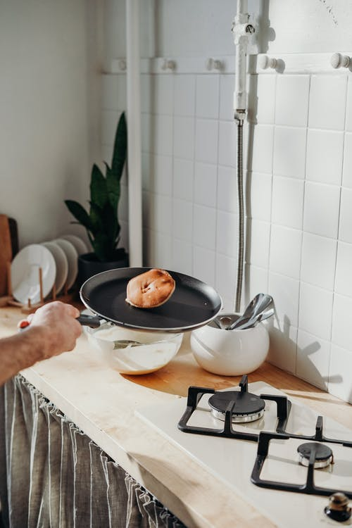 Person Holding a Frying Pan With Pancake