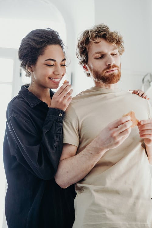 Man and Woman Holding Bread