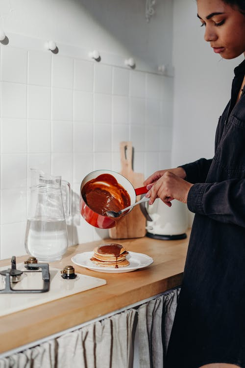 Woman Pouring Chocolate Dip on Pancakes