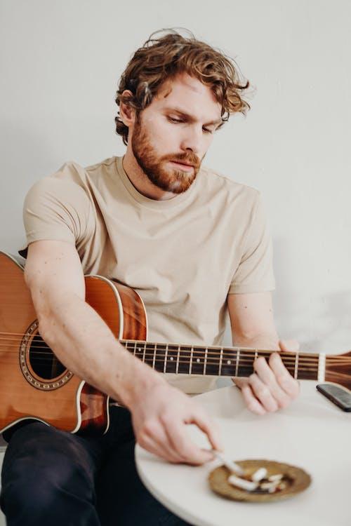 Hombre Tocando La Guitarra Acústica Marrón Mientras Fuma